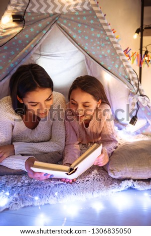 Photo of a happy young woman with her little daughter girl lies on floor reading book. Christmas concept. #1306835050