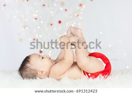 Photo of a healthy, chubby baby lying on his back on a white sheepskin, playing with his toes, wearing a red cloth diaper/nappy with a lit, white Christmas tree in the background.