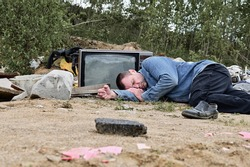 Photo of a homeless man on the background of trash and garbage outdoors. Model is lying on the ground and looking at the camera