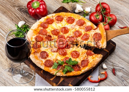 Photo of a hot pizza on wooden background. Toned image