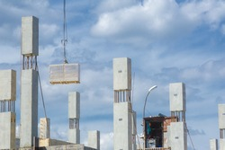 Photo of a house under construction. Building under construction. Lifting cranes and building under construction. big construction site.