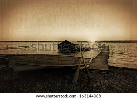 Photo of a lake shore dock with a row boat and boat shelter at sunrise. Photo has been enhanced with a sepia tone an textured for a grungy, vintage old photo  look.