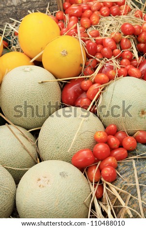 Photo of a large group of fruit and vegetables on straw