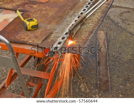 photo of a man flame cutting steel plate