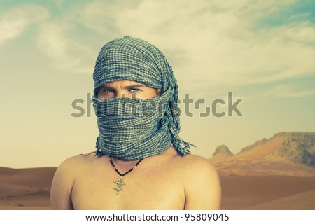 Photo of a man in Bedouin scarf in desert - stock photo