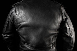 Photo of a man in black leather biker jacket standing on neon lightened night street background rear view.