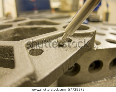 photo of a man inspecting steel part