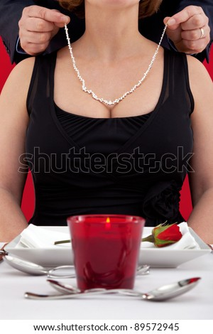 Photo of a man putting a diamond necklace around the neck of his wife , who is sat at a table in a restaurant celebrating her birthday or their wedding anniversary.