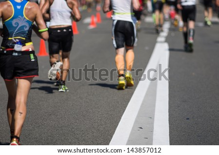 Photo of a marathon competition during an ironman. Focus on the foreground , no faces recognizable. Shallow depht of field.