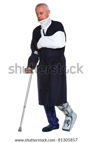 Photo of a mature male with various injuries using a crutch, he's wearing a neck brace, arm sling and leg cast and has a black eye, isolated on a white background.