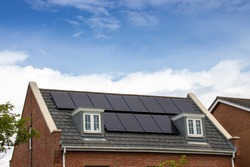 Photo of a modern British house in the UK with electrical solar panels on the roof on a bright sunny day with clouds in  the sky