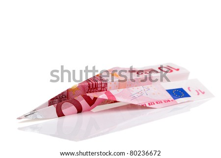 Photo of a paper plane made from a ten Euro banknote, isolated on a white background.