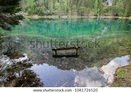 Photo of a partially sinked bench, as found at the Green Lake, in Styria, Austria. Crystal clear mountain lake, emerald green water, landscape reflecting in it.  #1081726520