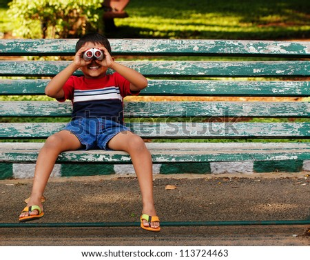 Photo of a playful and cute young asian/indian boy looking into binoculars and having fun at a park. The child is sitting on a old wooden chair in a garden on a sunny afternoon and having good time.