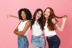 Photo of a pleased cheery young three multiethnic girls friends posing isolated over pink wall background.