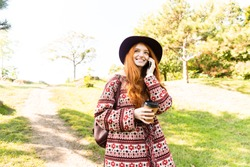 Photo of a pleased positive cutie young student redhead girl in autumn park talking by mobile phone.