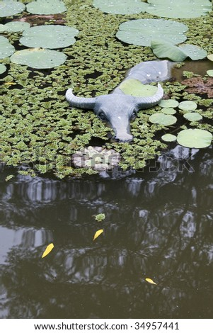 Photo of a pond with lotus plant and a stone status of a water buffalo.