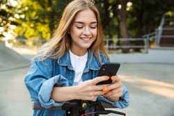 Photo of a positive cheerful teenage girl in park walking on scooter using mobile phone.