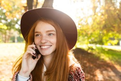 Photo of a positive cutie young student redhead girl in autumn park using mobile phone talking.