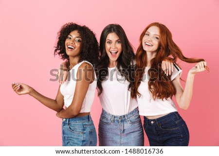 Photo of a positive smiling pleased young three multiethnic girls friends posing isolated over pink wall background. ストックフォト ©