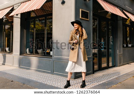 Photo of a pretty blonde on the street in a semi-profile, looking confusedly down. Photo of a young lady in fashionable clothes in full growth.
