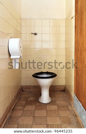 Photo of a public toilet with part of the seat missing, the floor, walls and bowl are stained and dirty.