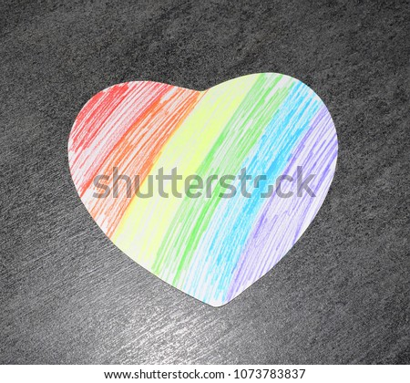 Photo of a rainbow heart on a dark background. Symbols of LGBT people.