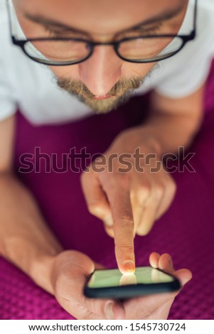 Photo of a rather serious young handsome man pressing something on the touch screen of his device mobile device