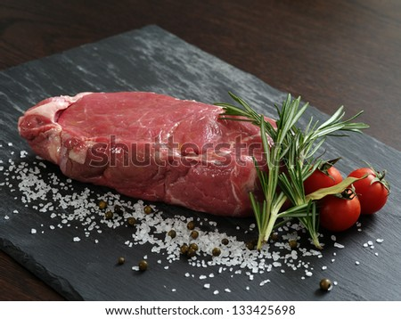 Photo of a raw thick sirloin steak with rosemary, cherry tomatoes, salt and peppercorns on a piece of black slate.
