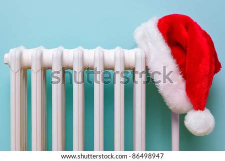 Photo of a red and white Father Christmas hat hanging on an old traditional cast iron radiator.