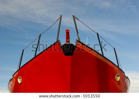 Photo of a red fishing boat in dry dock against blue sky