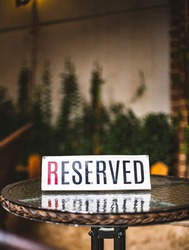 photo of a reservation sign on wooden table outdoor area of a cafeteria with flowers and plants in background - reservation for crowded restaurant sign
