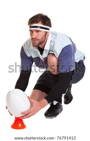 Photo of a rugby player placing the ball on a kicking tee, cut out on a white background.
