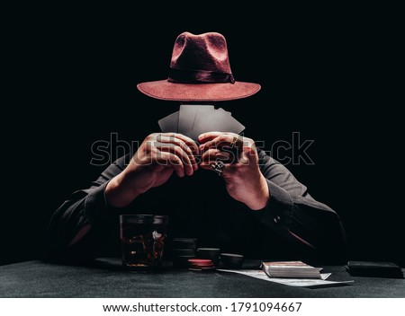 Photo of  Photo of a shaded gangster in black shirt and hat playing poker and holding black cards with game chips and money.