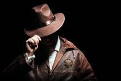 Photo of a shaded sheriff officer with badge in jacket putting on cowboy hat on black background.