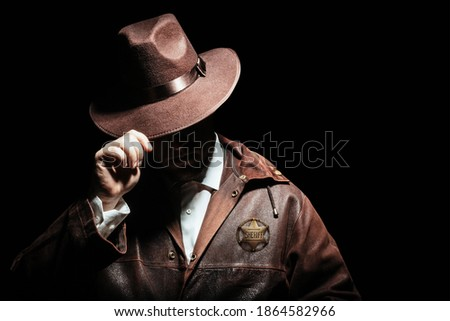 Photo of a shaded sheriff officer with badge in jacket putting on cowboy hat on black background. Stock fotó ©