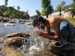 Photo of a shirtless man washing face in river, Indian guy washing face with water in the nature