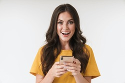 Photo of a shocked positive emotional surprised young woman posing isolated over white wall background using mobile phone.