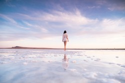 Photo of a slender woman from the back with reflection in the water. A girl walks on a salt lake at sunset.