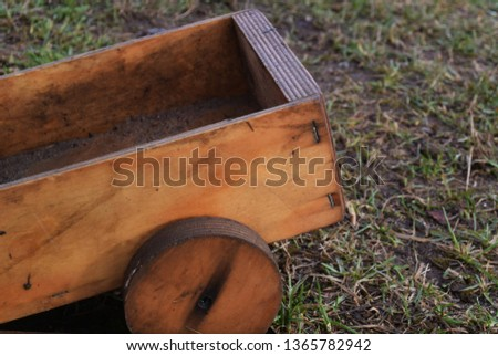 Photo of a small toy wooden cart on wheels on the background of grass #1365782942