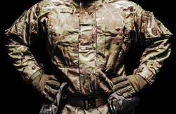 Photo of a soldier in multicam camouflage tunic  and tactical belt with pouches on black background.