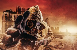 Photo of a stalker in jacket and gloves in damaged gas mask with filter reaching out his hand to camera on destructed apocalyptic wasteland city background.