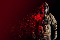 Photo of a stalker soldier in soviet gas mask, jacket and armored vest standing and dissolving with red highlights on one side.