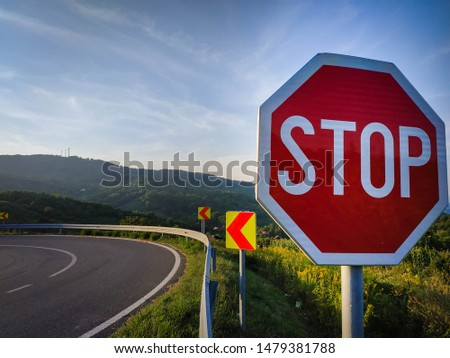 Photo of a stop road sign with sign of sharp turn