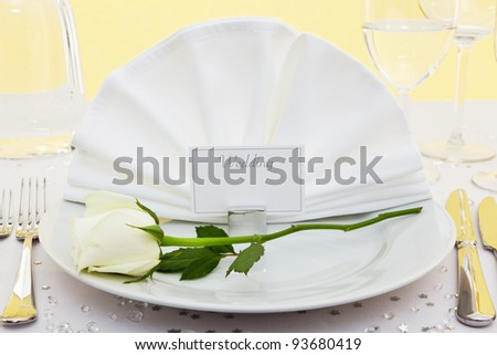 Photo of a table place setting for a wedding with a white rose on the plate.
