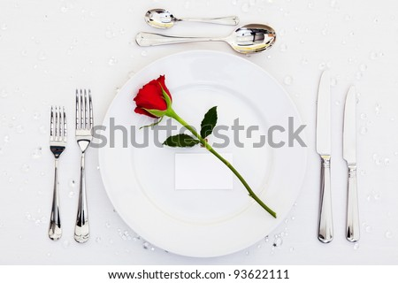 Photo of a table place setting with a red rose and blank card on the plate. Add your own message to the place card.