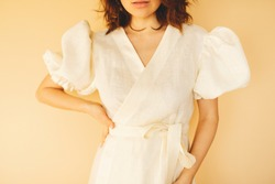 Photo of a teenage female posing in milk or cream color dress with puff sleeves and belt. Details of women clothing. Close up fashion details of woman wearing elegant dress on yellow background.