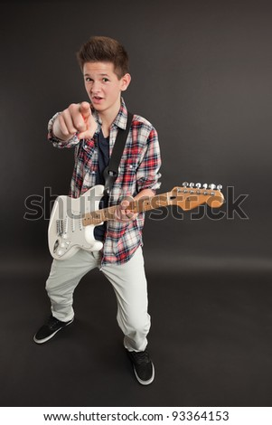 Photo of a teenage male playing a white electric guitar and pointing at you.