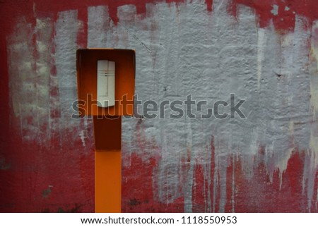 Photo of a throughput device in an orange case against a red wall with spots of paint