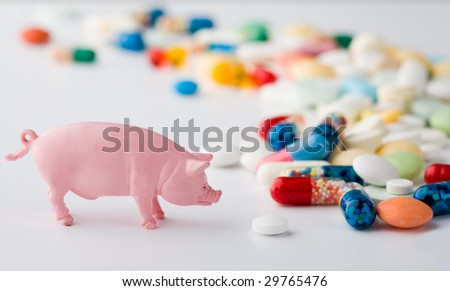 Photo of a toy pig standing near pile of colorful pills